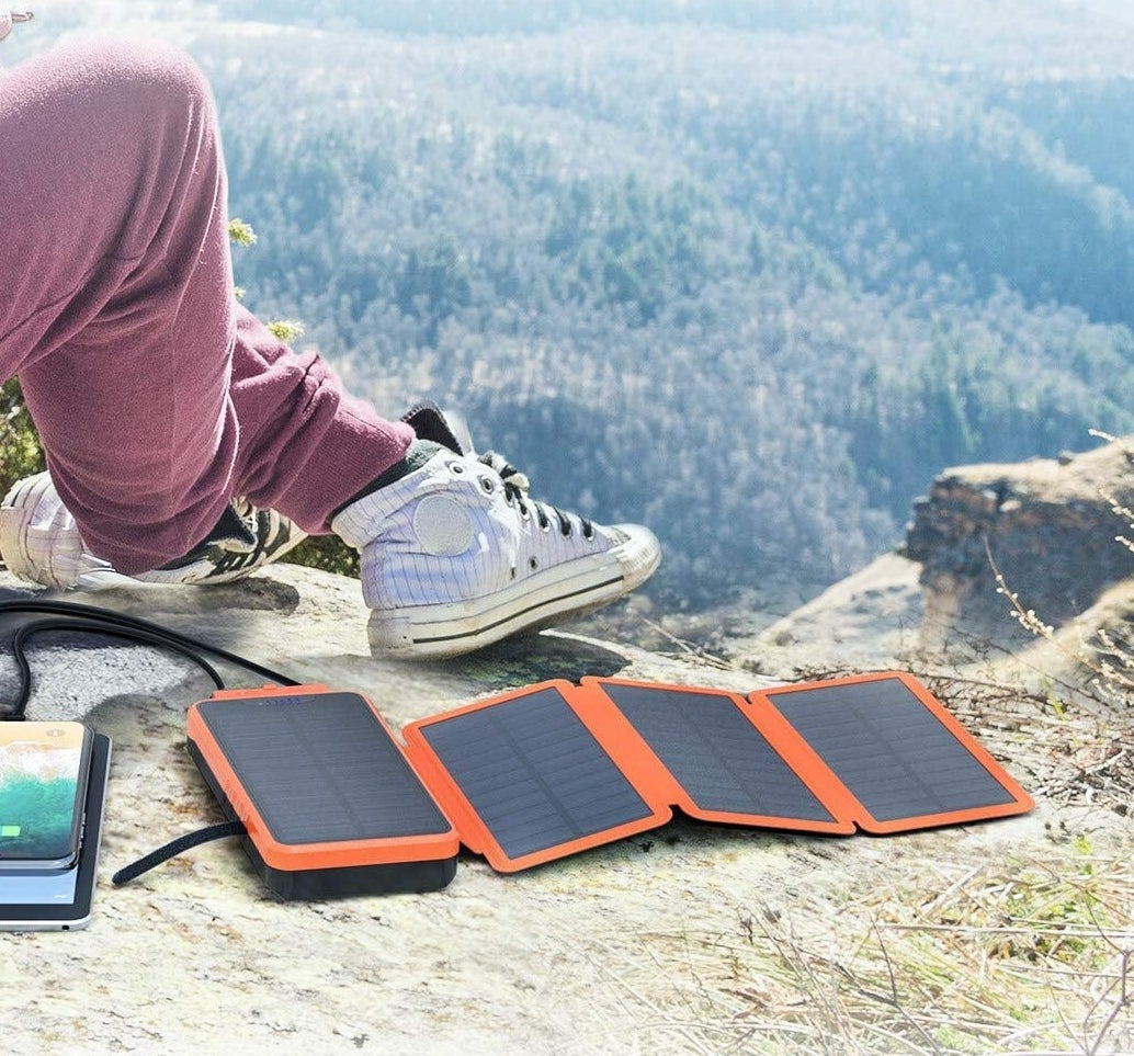 The solar power bank laid out on some rocks in the wilderness