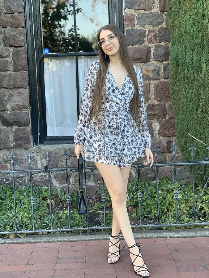A reviewer wearing the long-sleeve black and white floral deep v-neck, ruffled romper