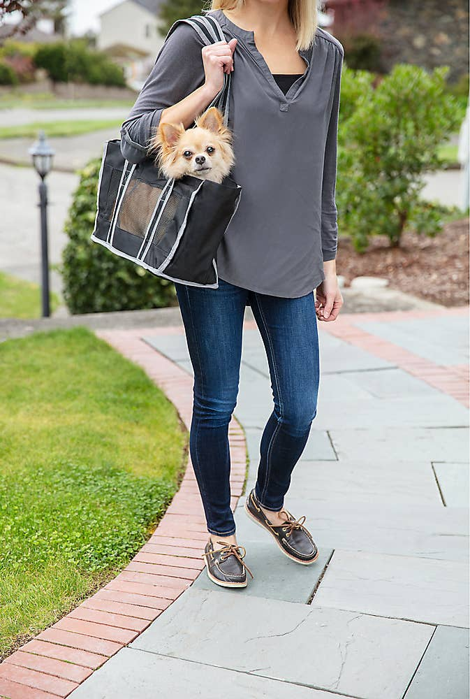 A small dog in a black bag with a person in blue, white and brown carrying it