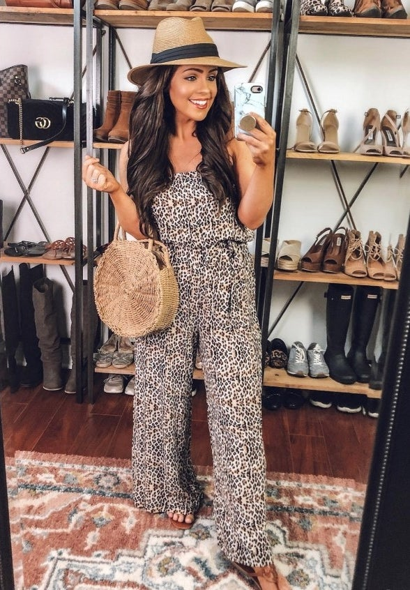 A reviewer wearing the leopard print women's strapless, wide-legged jumpsuit
