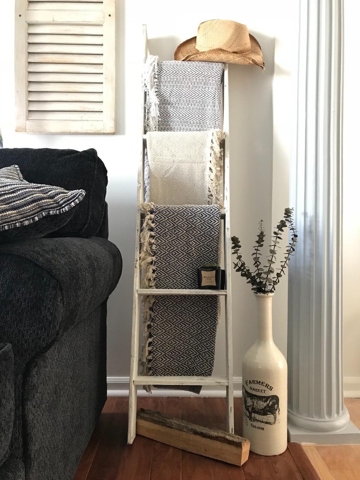 靠在墙上的梯子,在起居室的每一个横档上放着一条毯子