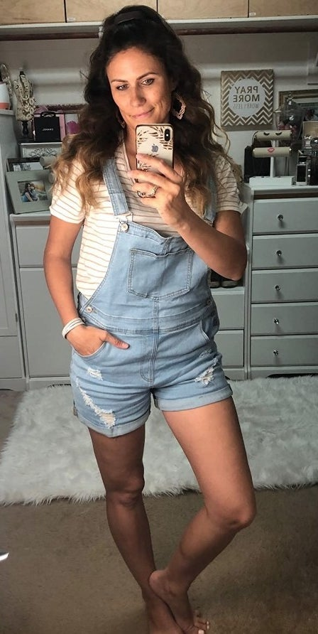 A reviewer wearing the light blue short overalls with adjustable straps and pockets