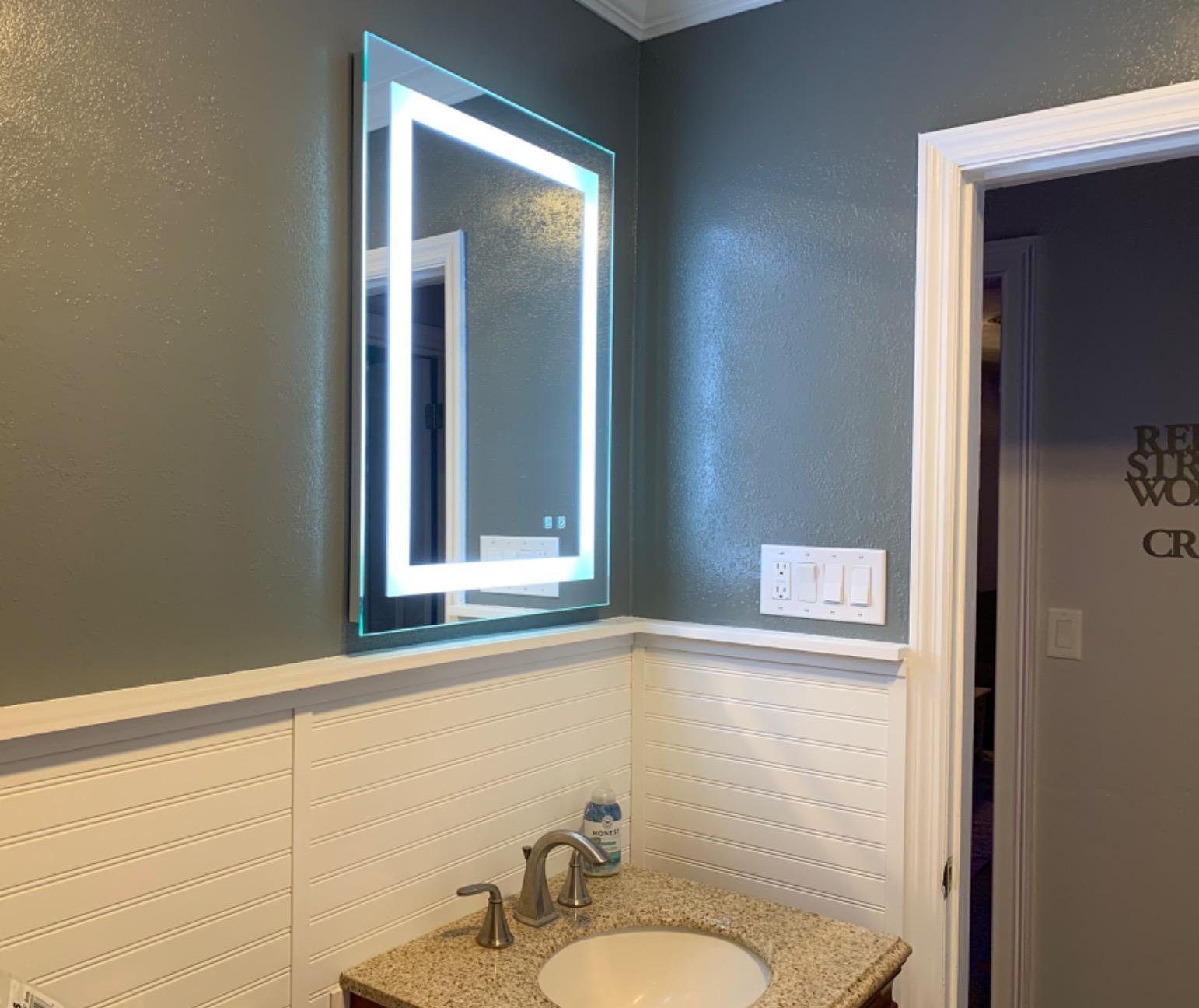 带有方形周长的镜子的LED灯悬挂在浴室水槽上