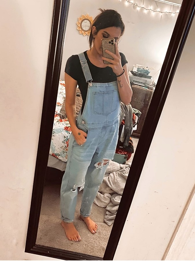 A reviewer wearing the distressed light blue overalls with adjustable straps and pockets