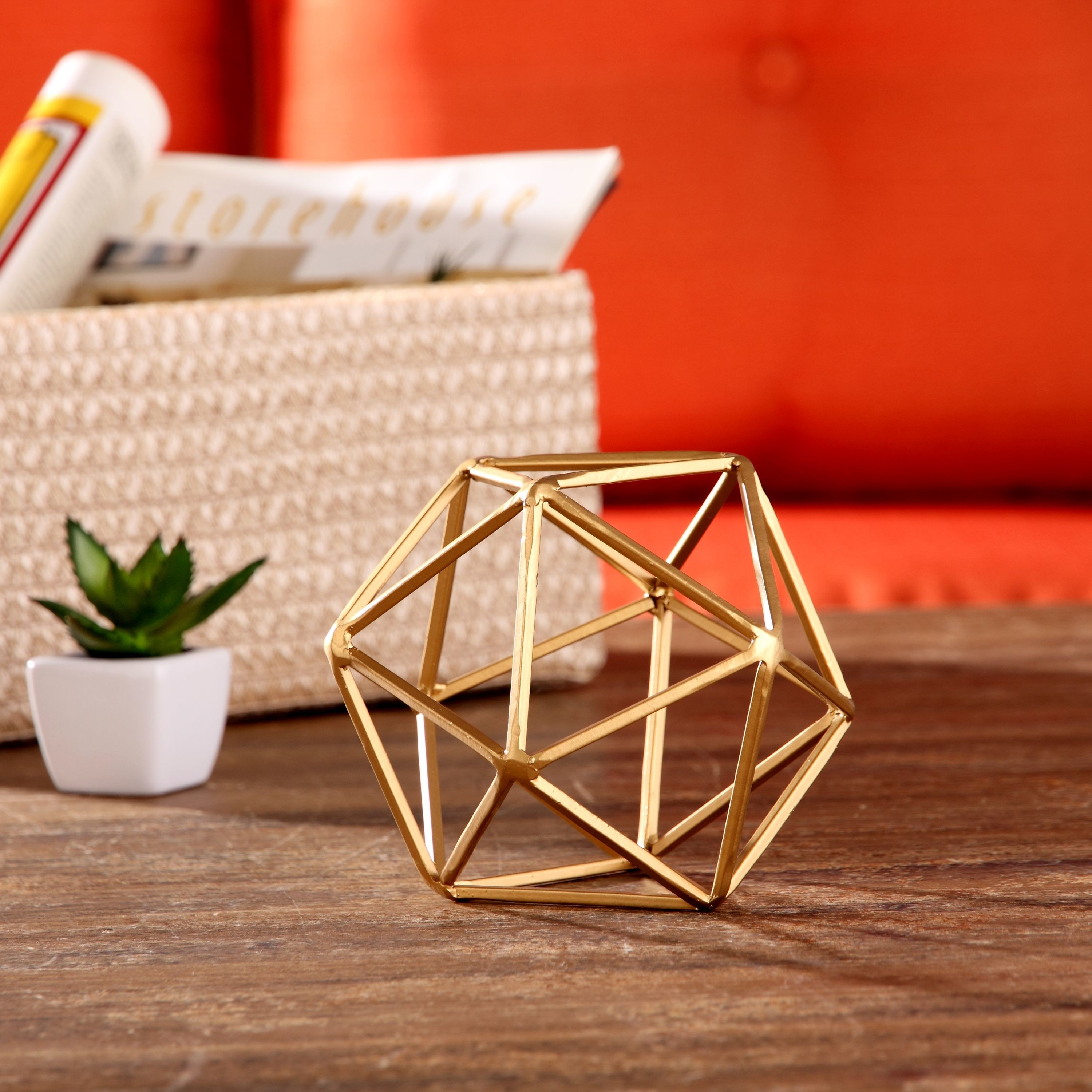 the geometric sculpture next to a tiny plant