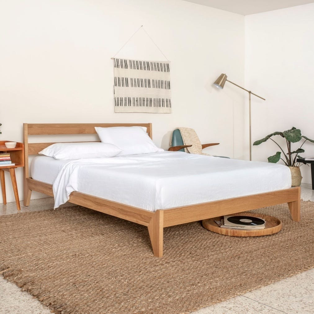 Wooden bed frame with white sheets on bed