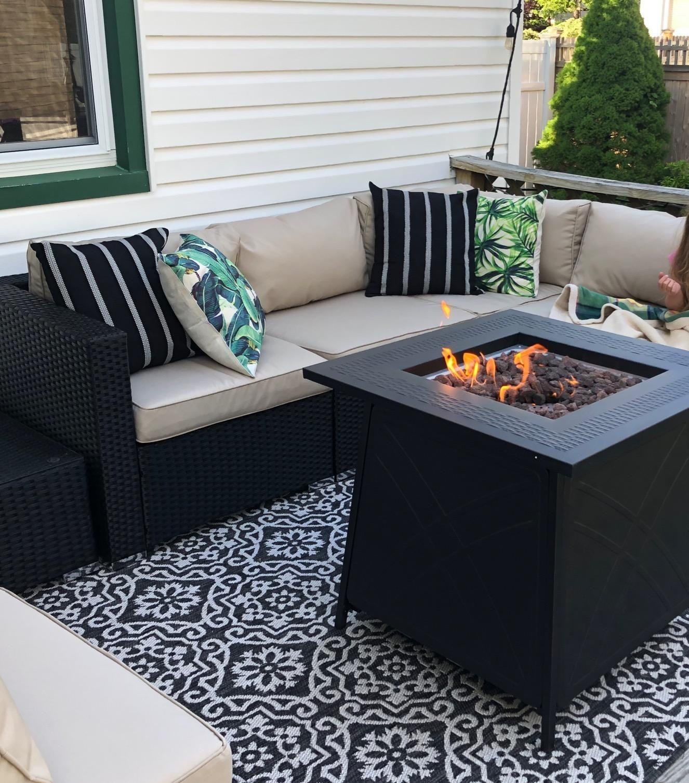 户外火坑和露台家具下的黑白印花地毯,图案为徽章图案
