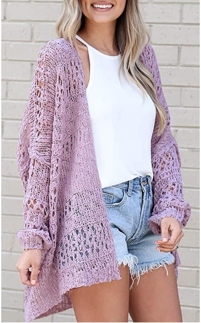 A model wearing a purple, boho-style, oversized knitted cardigan