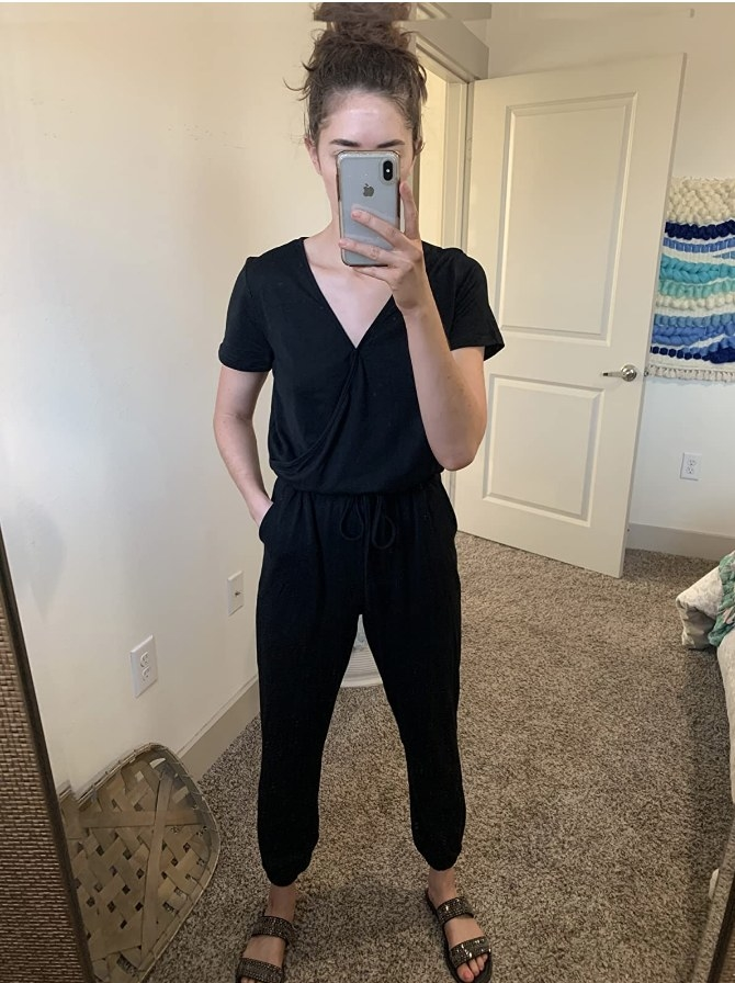 A reviewer wearing a black v-neck short sleeve jumpsuit with pockets