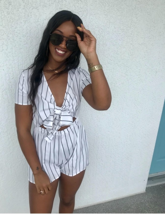 A reviewer wearing the black and white stripe v-neck, front tie romper