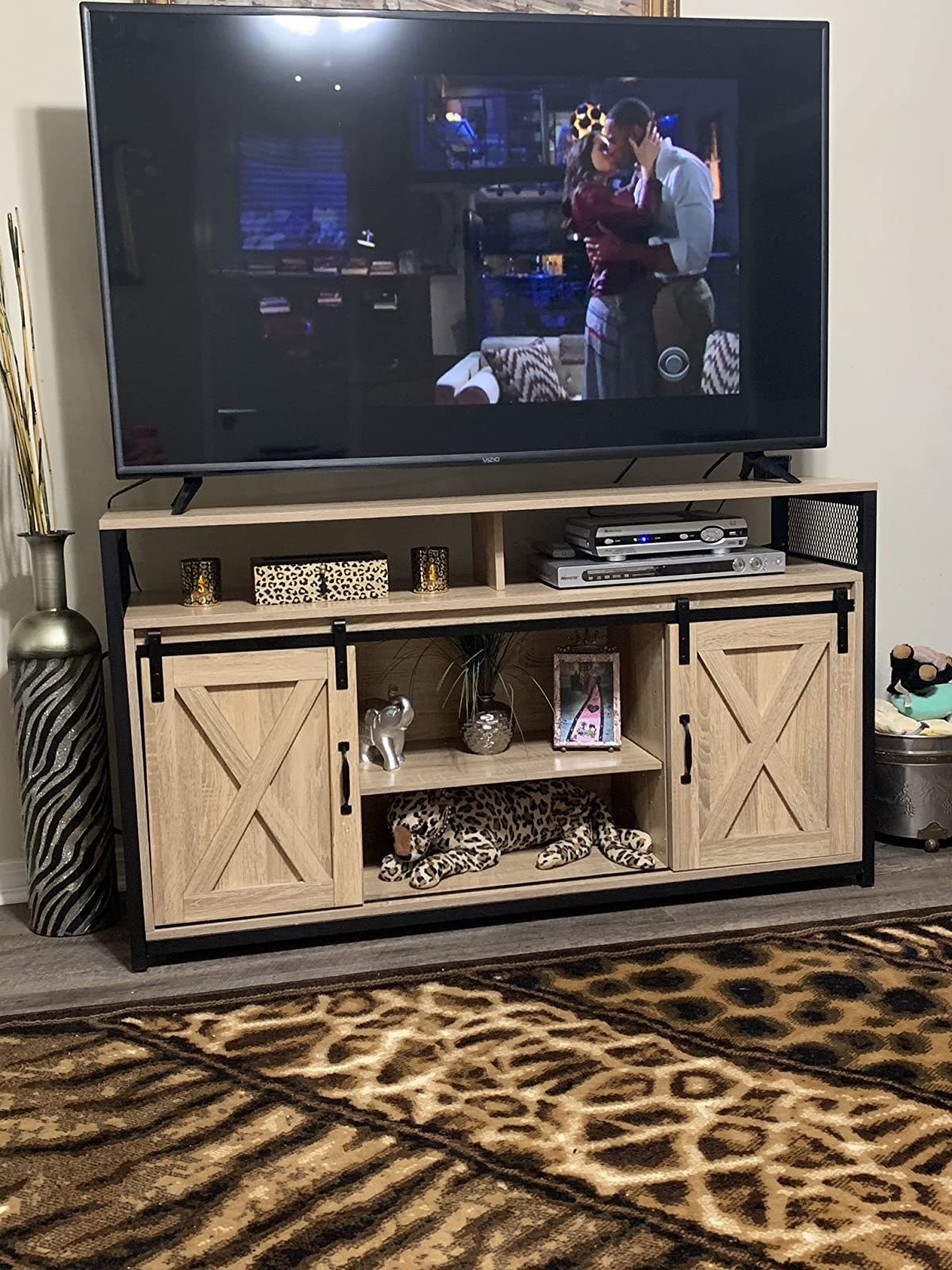 The TV stand supporting a TV with two open shelves and sliding barn doors on either side