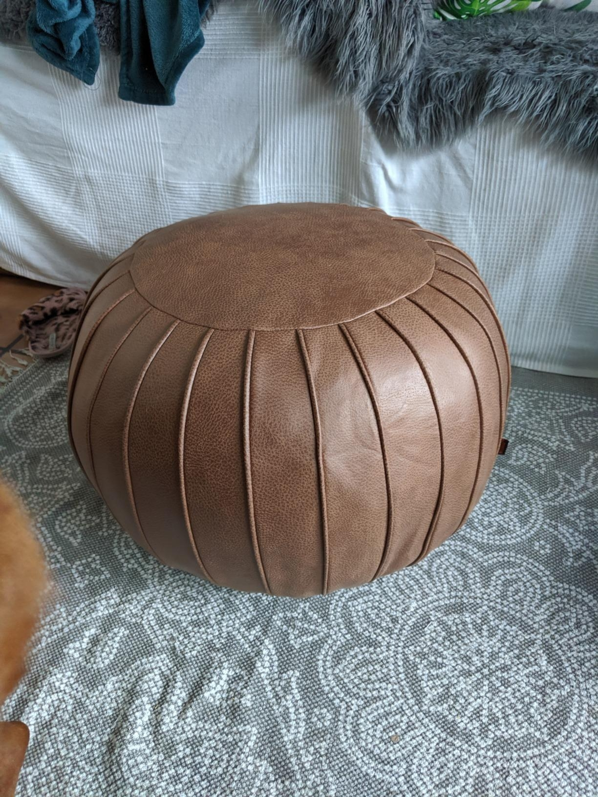 The brown circular pouf with a vertical line pattern around the entire thing
