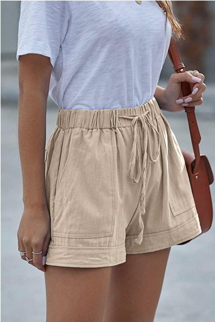 A model wearing a pair of khaki drawstring shorts with pockets