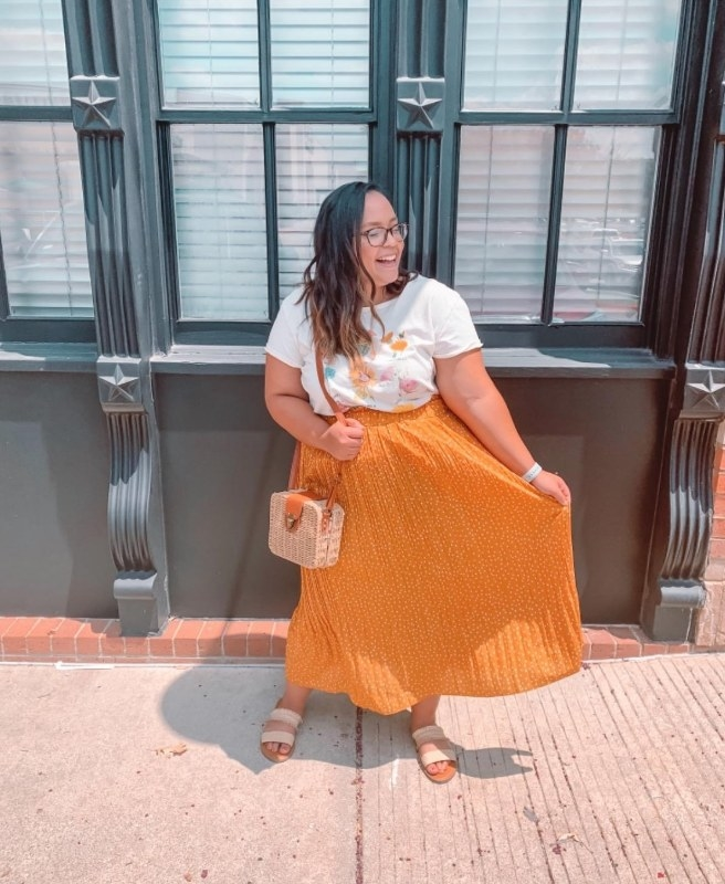 A reviewer wearing a mustard-yellow, polka-dotted midi skirt