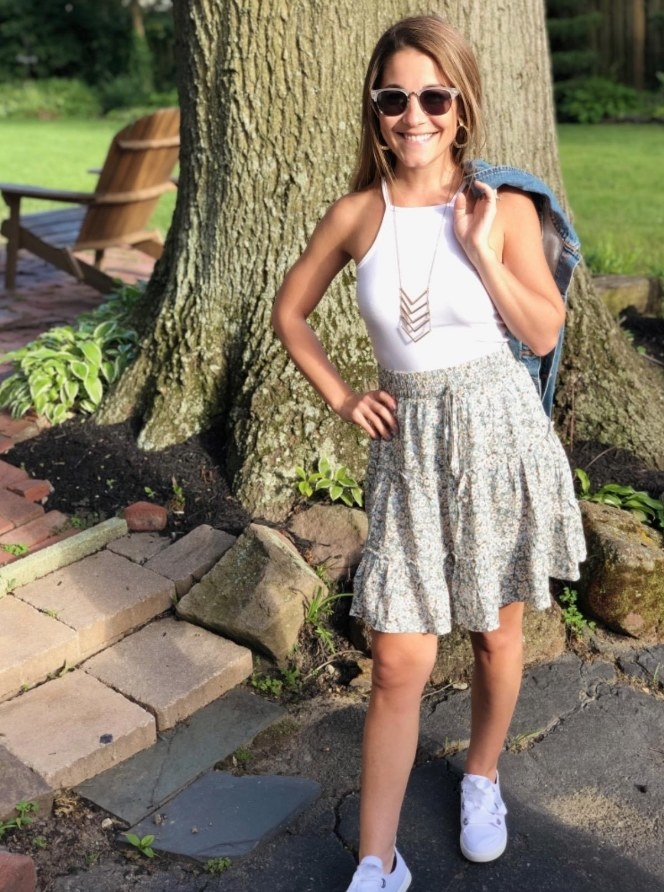 A reviewer wearing the light floral tiered skirt with a drawstring waist