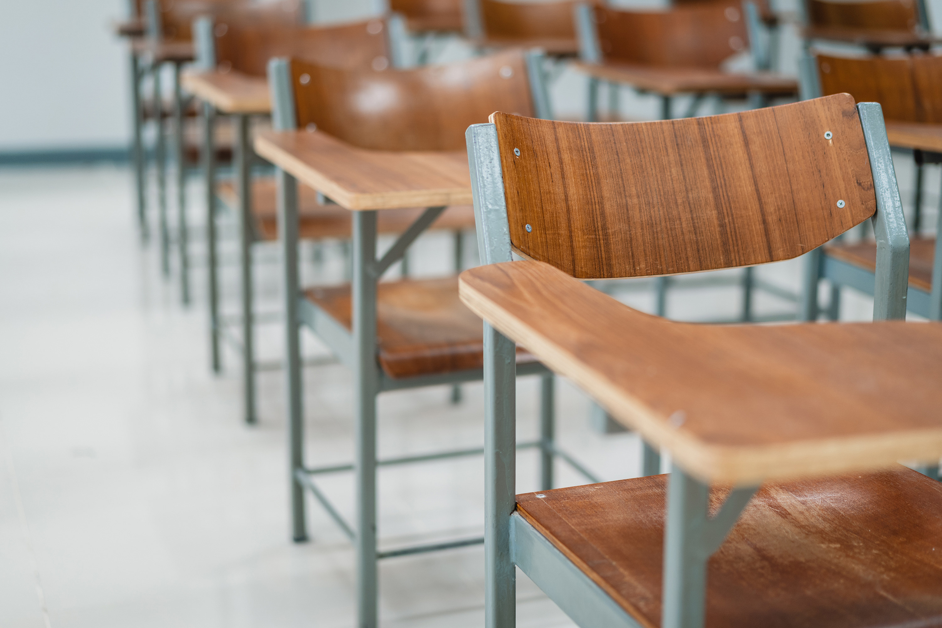 wooden school desks with attached chairs