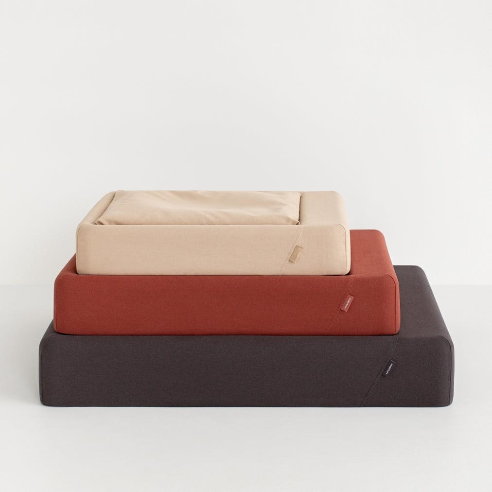 Three dog beds in gray, red and beige from larger size to smallest size top to bottom