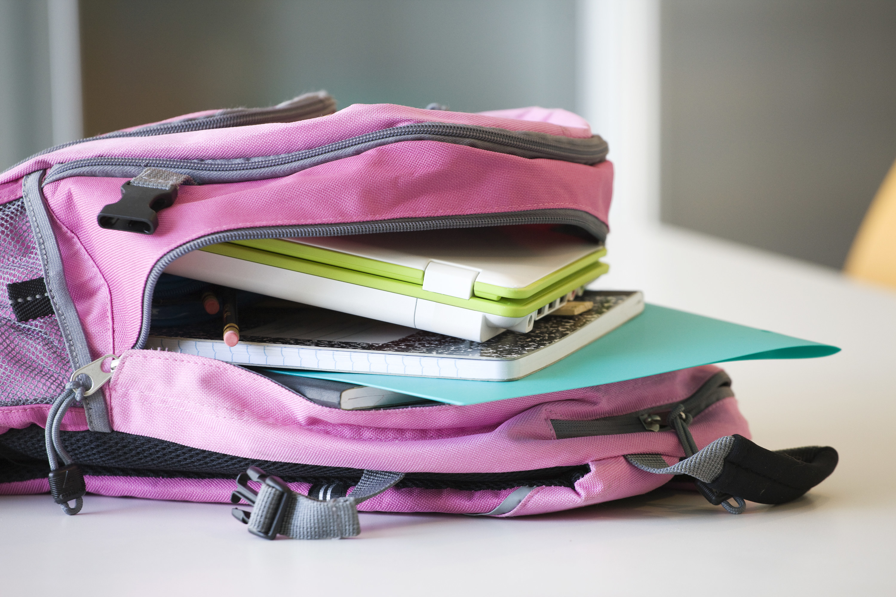 pinkish purple backpack laying on a desk unzipped, showing school supplies inside