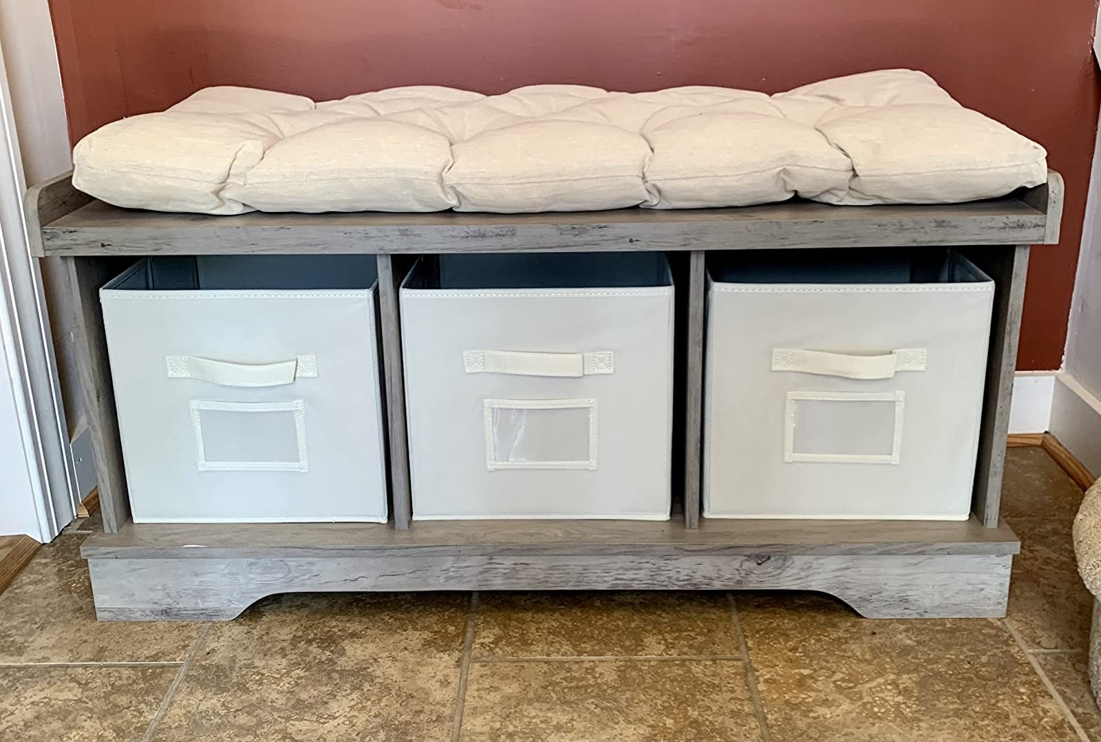 The bench with a cream-colored cushion and three matching storage bins underneath