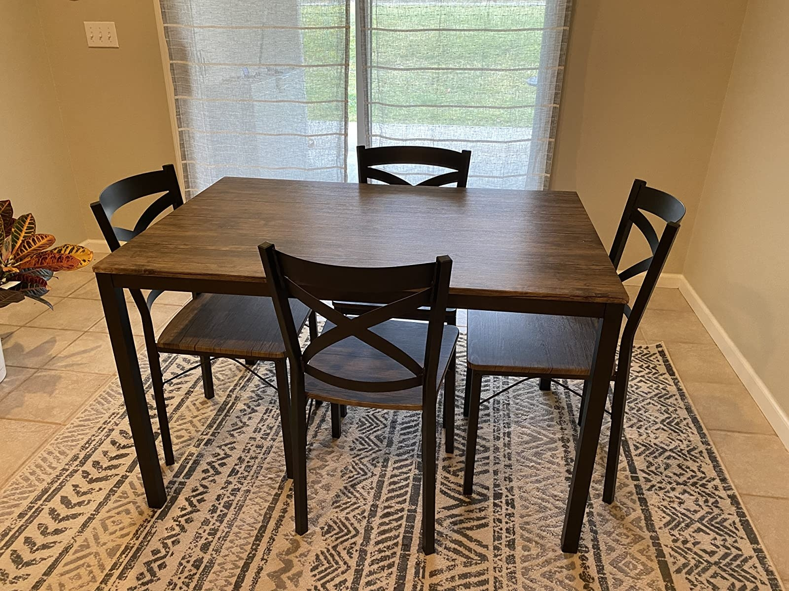 The dinning set with a table and four chairs that each have wood surfaces and black metal frames