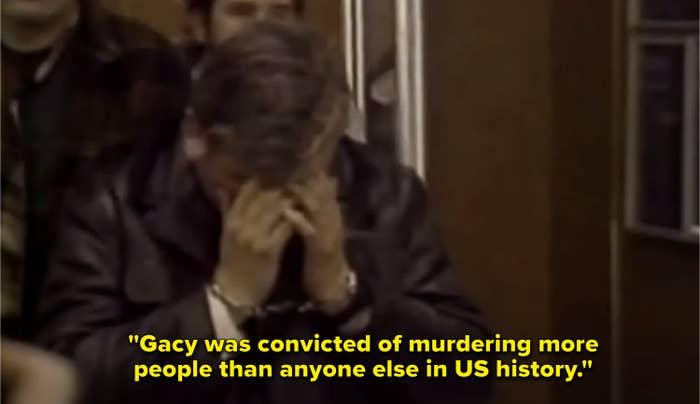 John Wayne Gacy walking to trial, handcuffed