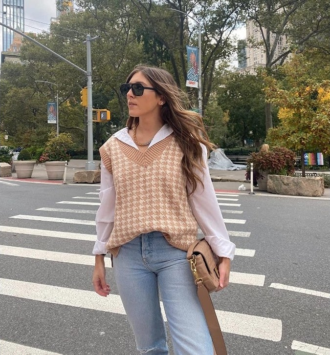 A reviewer wearing a khaki pullover houndstooth knit sweater vest