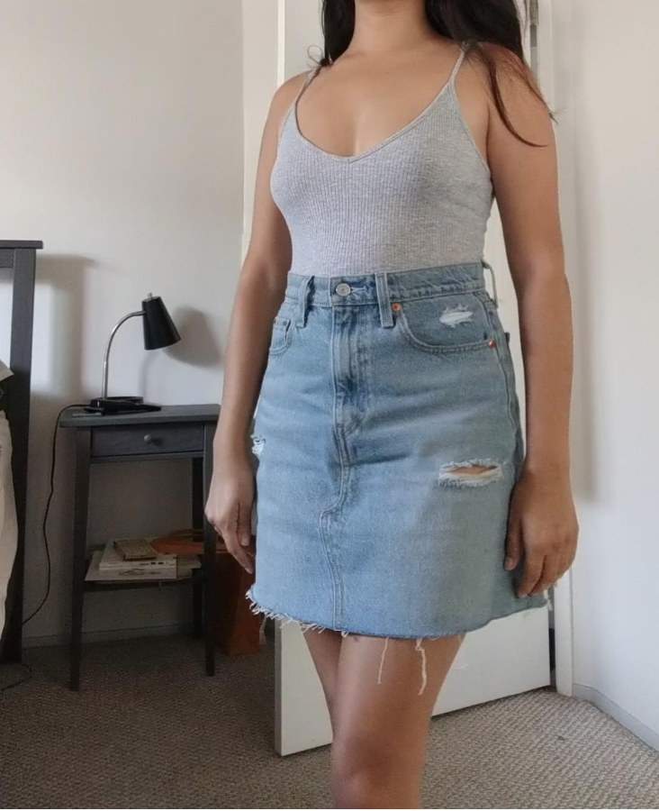 A reviewer wearing the light wash distressed high-rise denim skirt