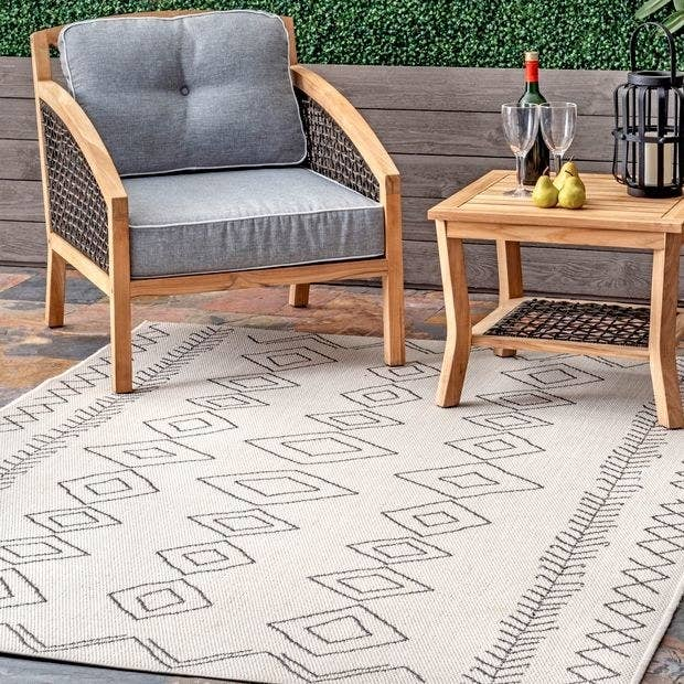 a white rug with a gray abstract design on it