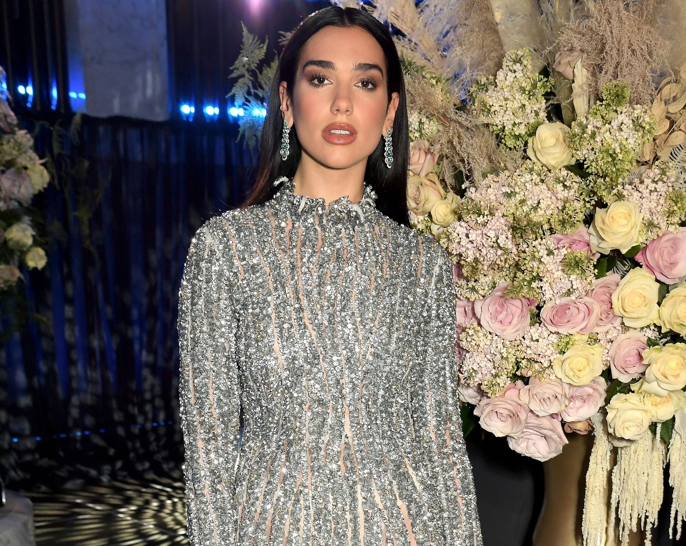 Dua keeps a straight face while wearing a silver dress