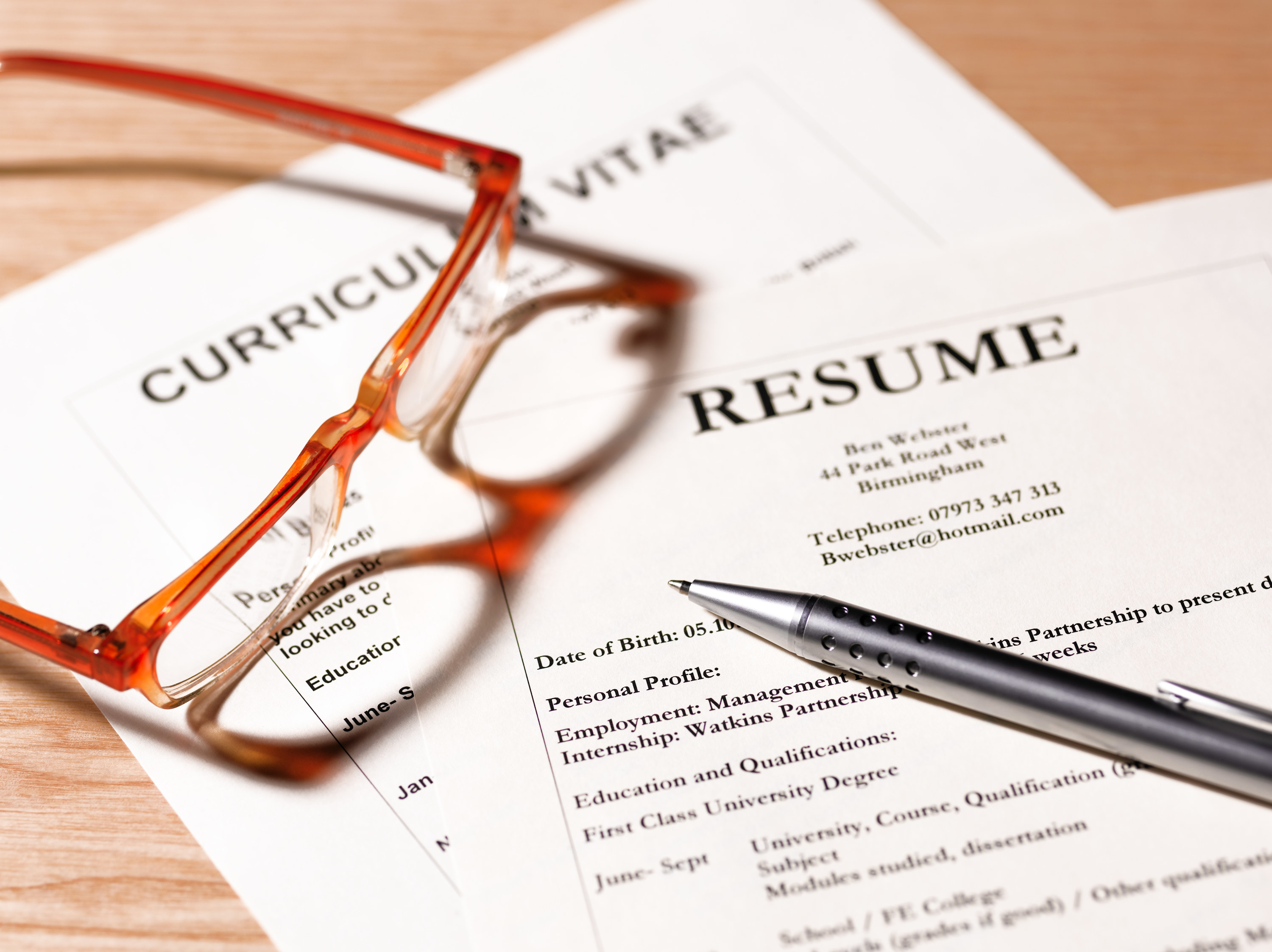 two resumes laying on a desk with red glasses and a pen