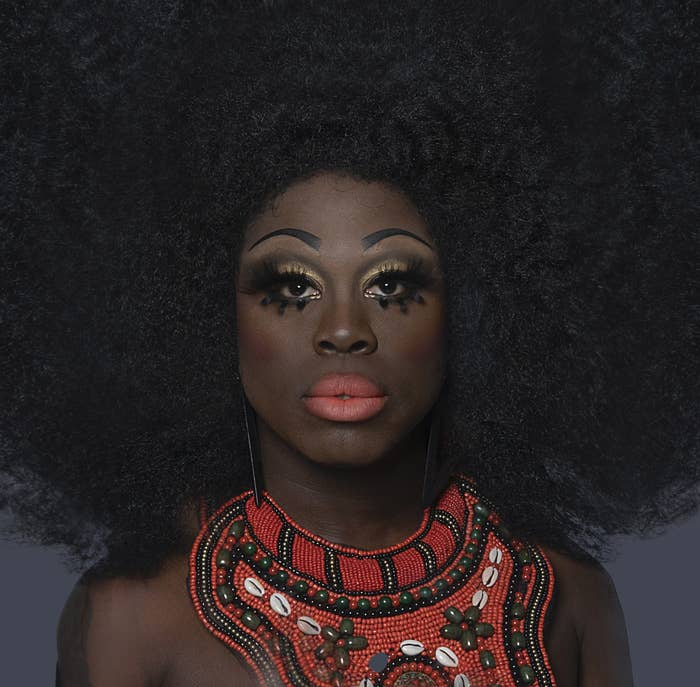 Close-up of Bob with a large Afro and coral lipstick with matching necklace