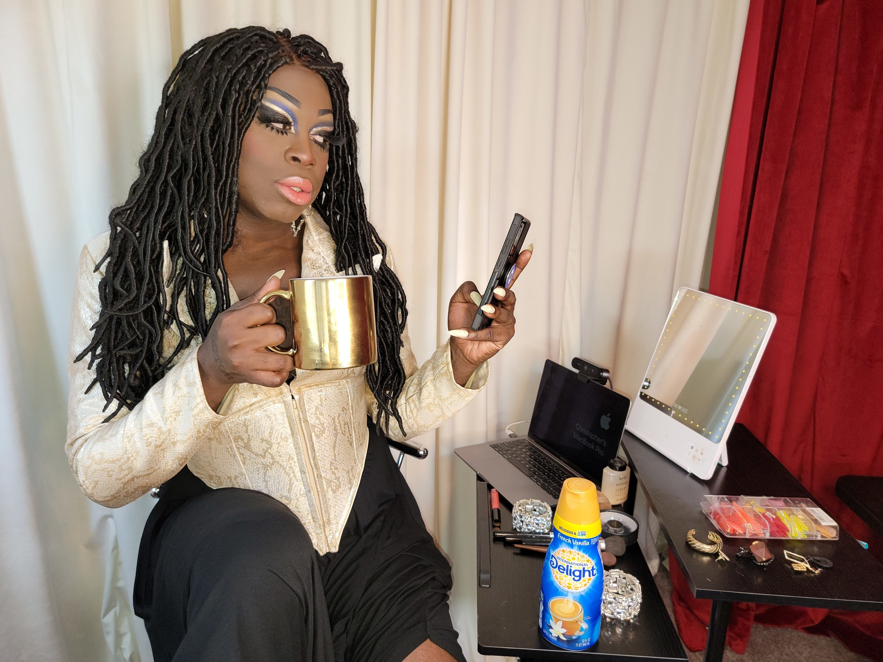 Photo of Bob looking at her phone while at her phone and sipping coffee from a gold mug