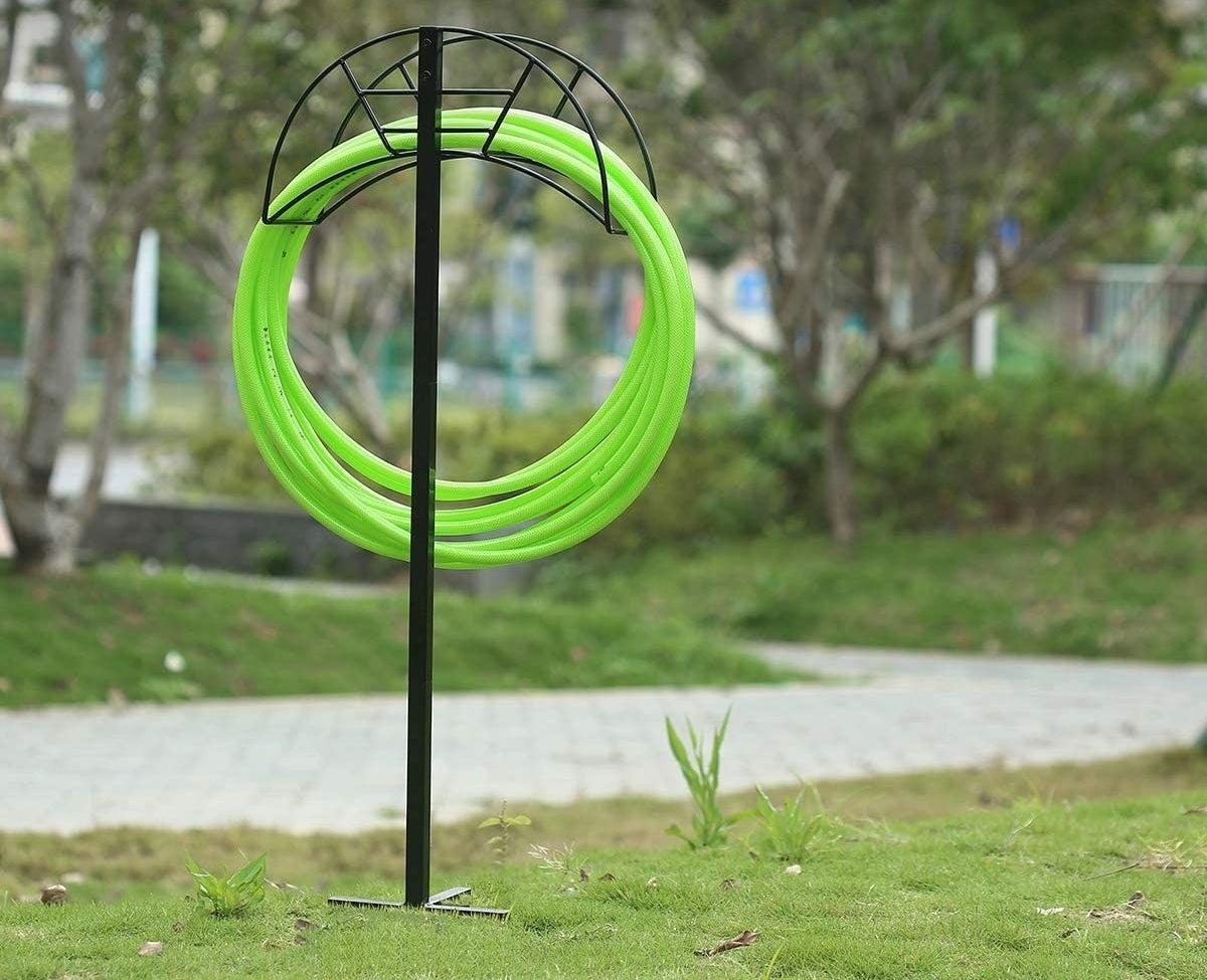 a free standing black metal hose holder