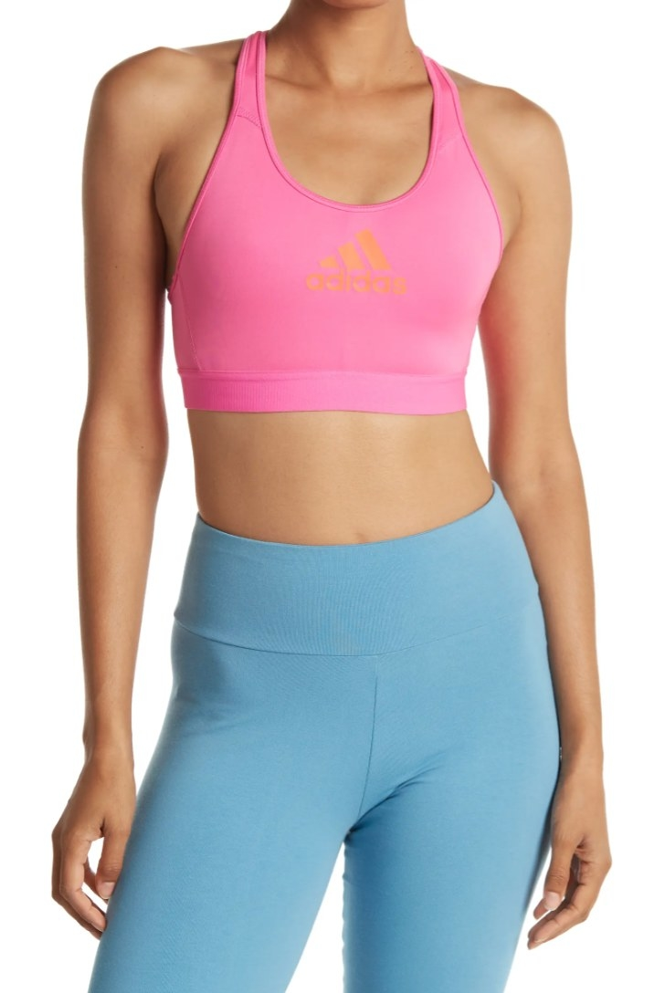 An Adidas sports bra in hot pink with an orange label