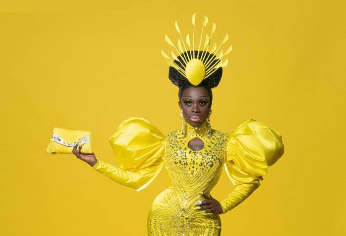 Bob in a stoned yellow gown with puffy sleeves and yellow crown holding a matching yellow purse, with a yellow background