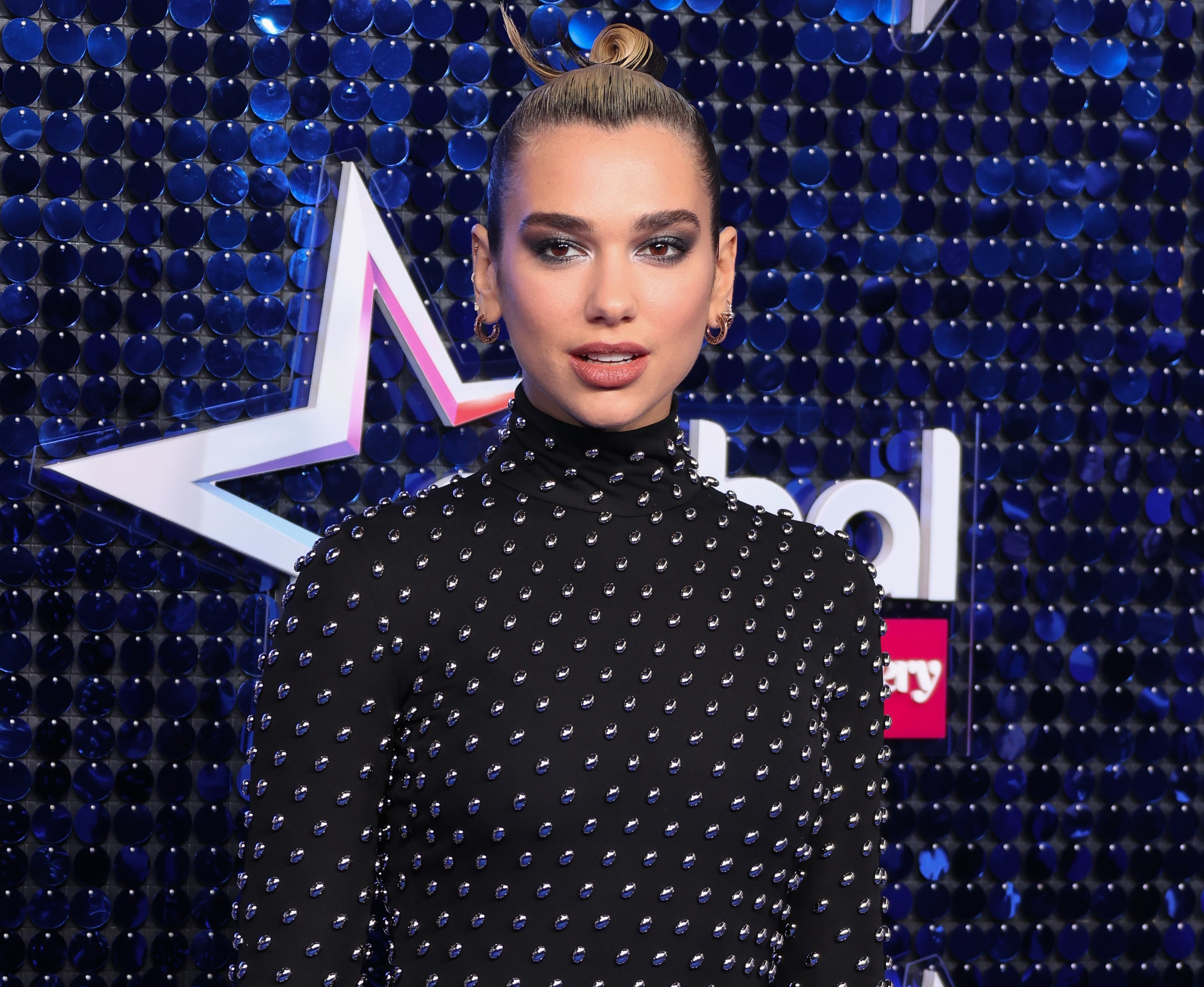 Dua looks serious in a black long-sleeve dress at an event