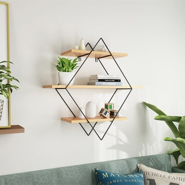 three wooden shelves attached by metal diamond shaped frame