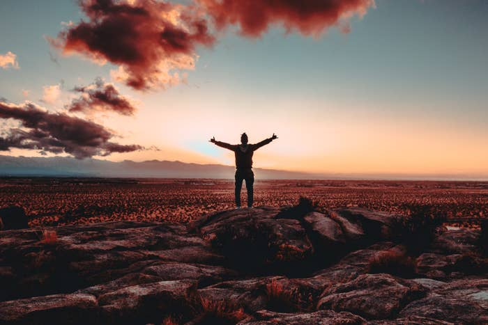 Person standing on a rock raising both hands to the sky