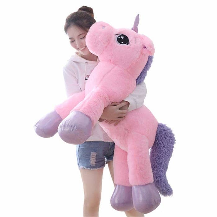 A person hugging the pink and purple unicorn plushie.