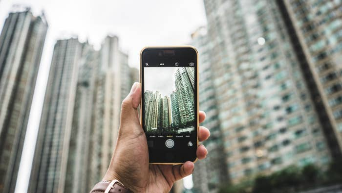 A photo of a smartphone's camera app taking a photo of many high rise buildings.