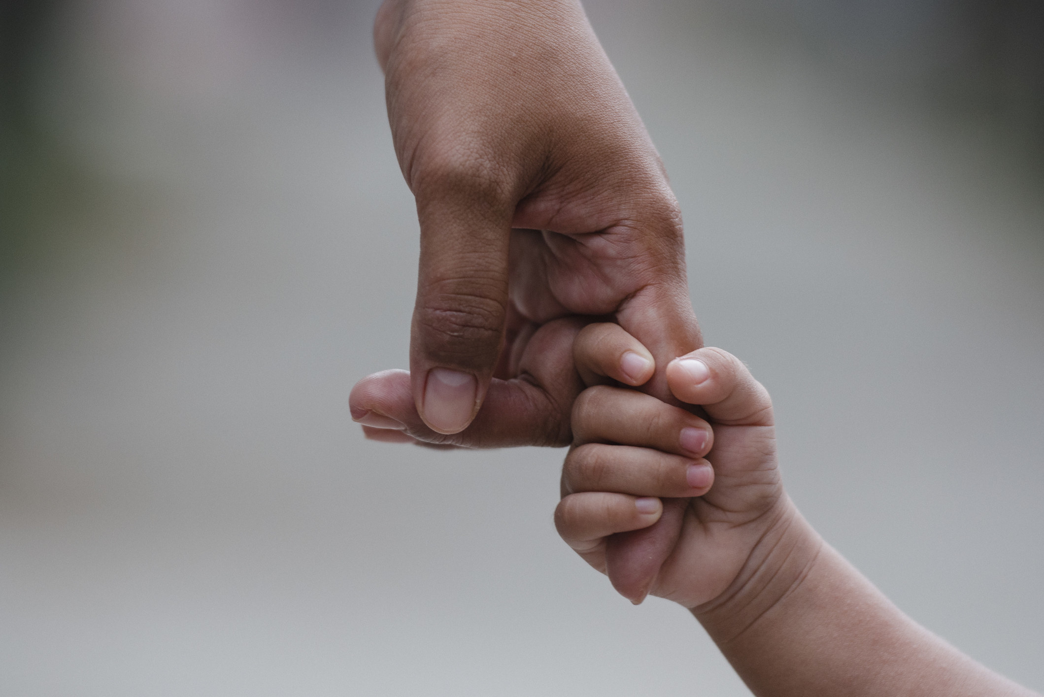 A child grips onto a parents hand tightly, not letting go