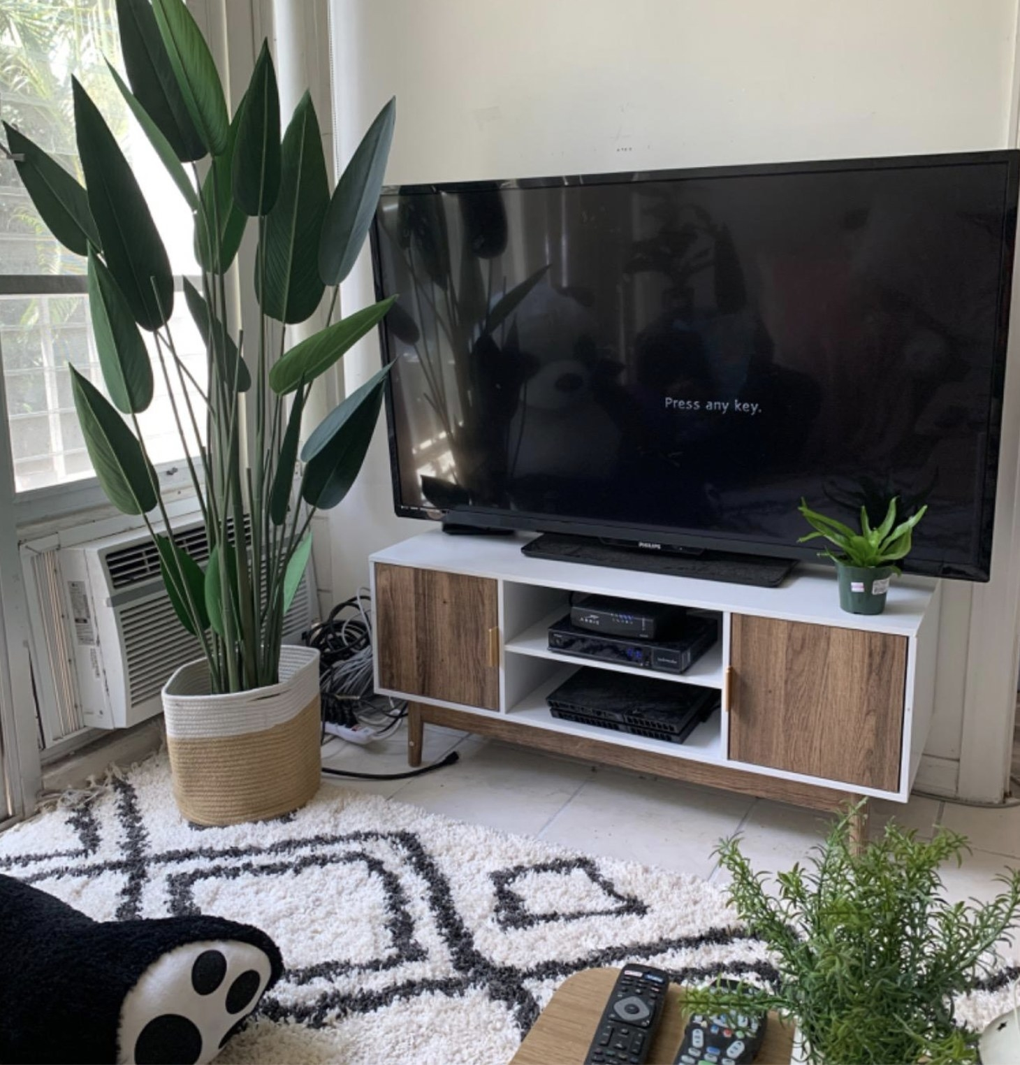 White TV stand with wood doors and legs in a reviewer's home