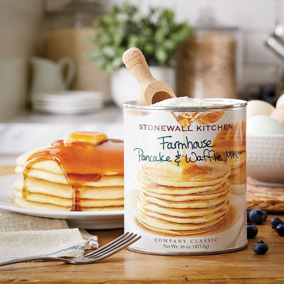 The tub of mix in front of a stack of pancakes