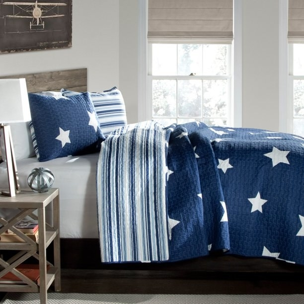 blue and white reversible quilt and shams on a bed