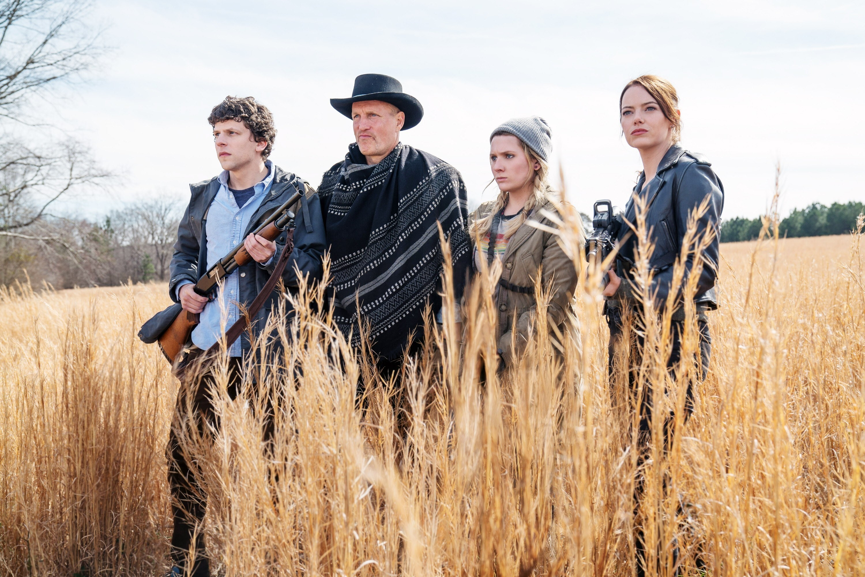 杰西·艾森伯格、伍迪·哈勒森、艾比盖尔·布雷斯林和艾玛·斯通手持枪站在田野里