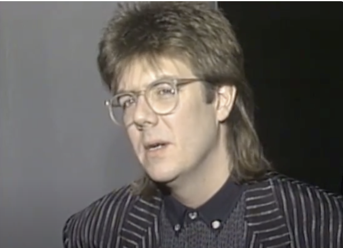 John Hughes with very '80s hair and glasses