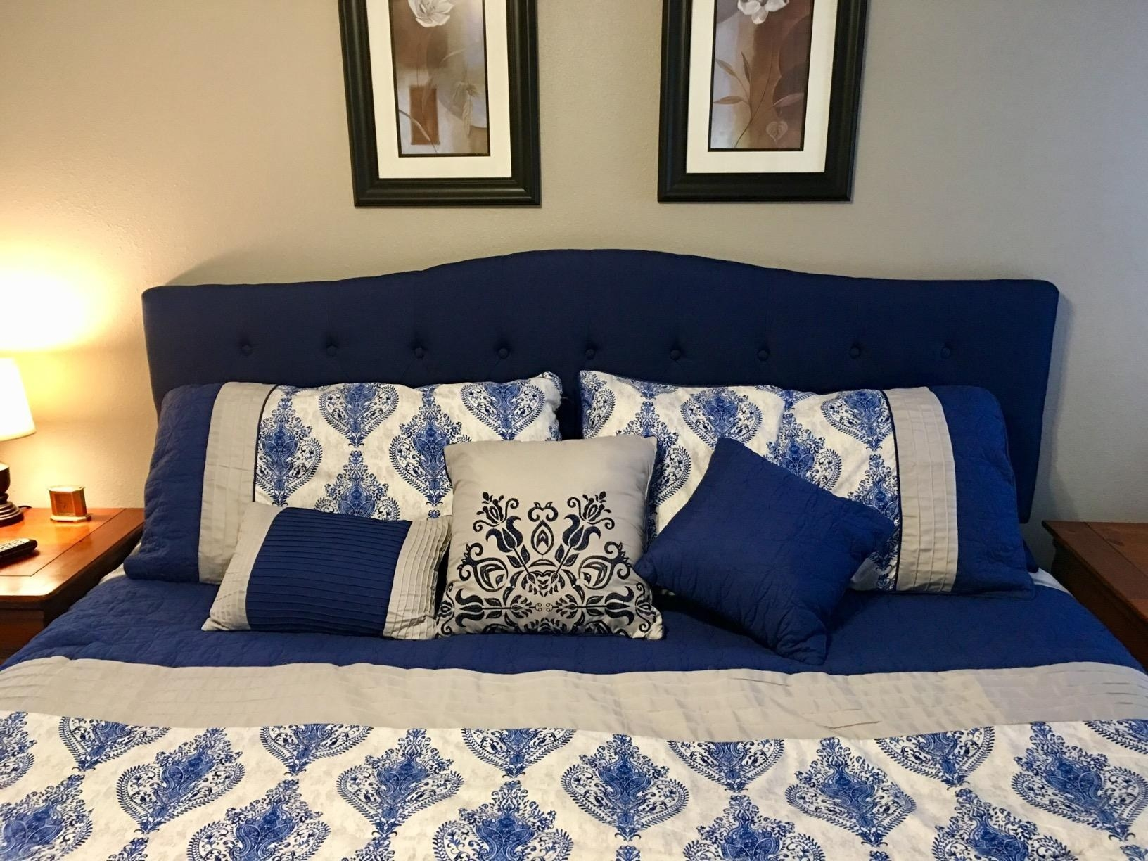 The blue tufted headboard with a slightly curved shape on a queen bed