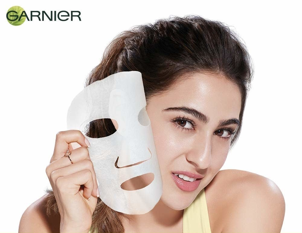 A person removing a sheet mask from their face.