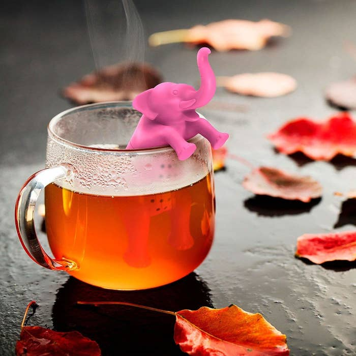 Elephant tea infuser half-submerged in a tea cup, while the other half hangs out.