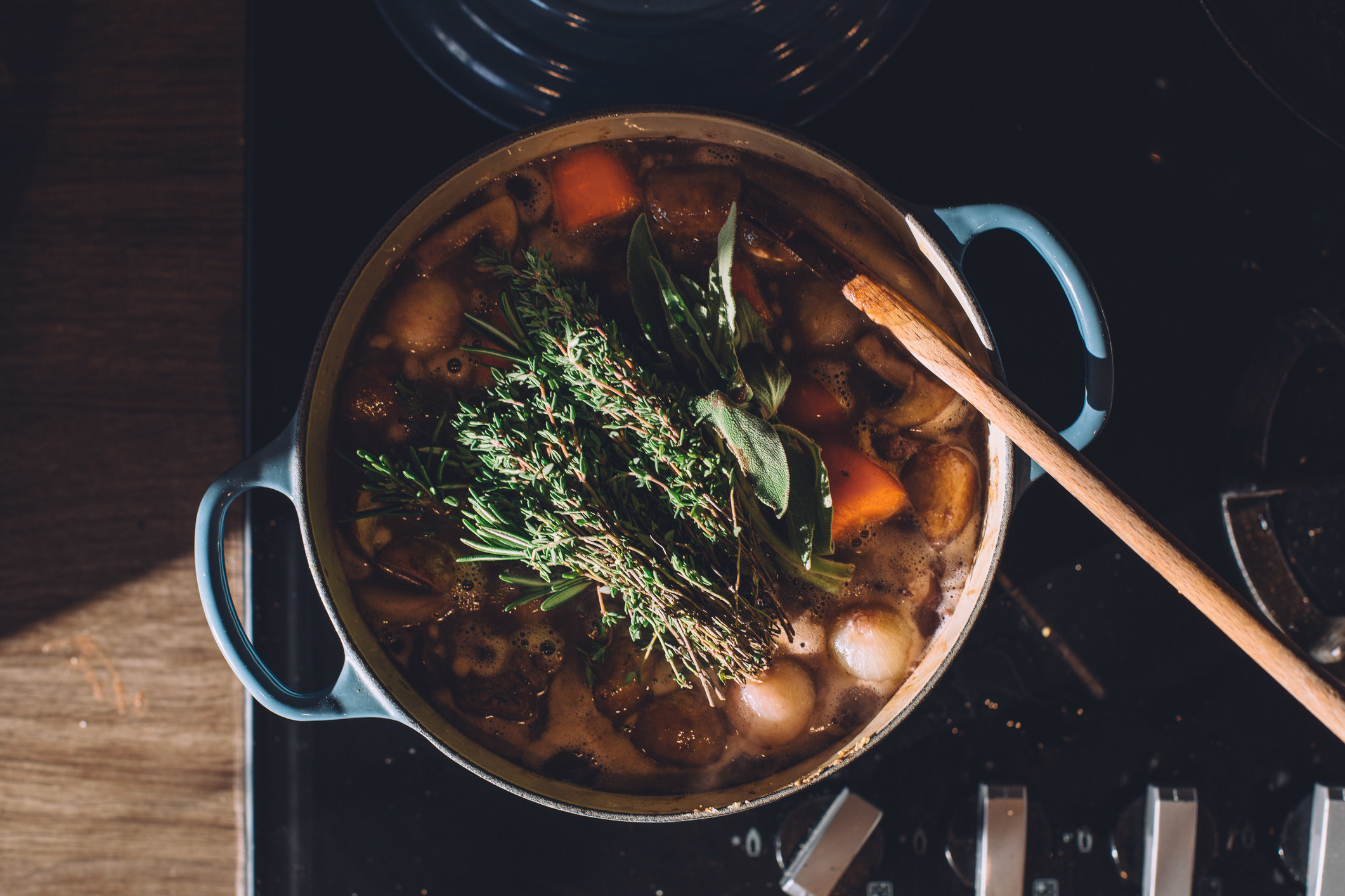 Soup in a big pot with fresh herbs
